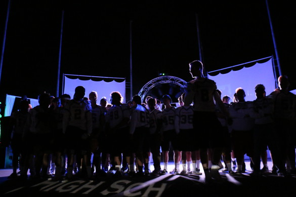 The football varsity team stands proudly on stage in front of their fellow supporting students. Photo by Sandra On