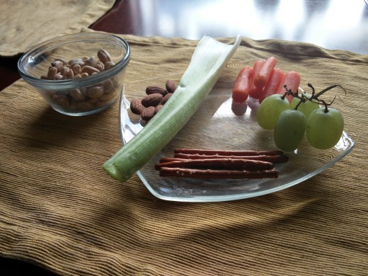 Celery, green grapes, carrots, almonds, pretzels and peanuts beautifully displaying themselves on a very nice glass plate. Photo taken by Benjamin Minch