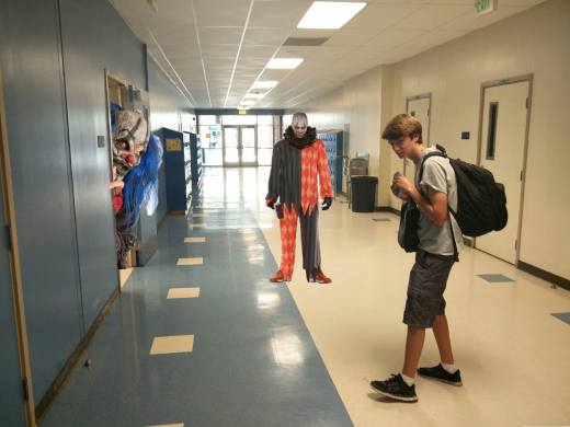 Daniel Sanders ('18) walking through the hallway, unaware that two clowns are watching him.