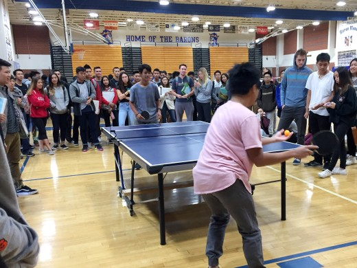 Two students battle it out on the ping pong table.